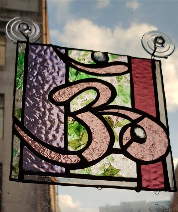 Om handmade stained glass panel in pink and confetti glass